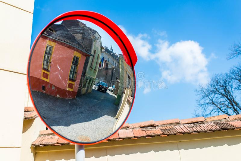 Visible passing car on the mirror on medieval street. Sighisoara, Romania-  23 March 2019: Visible passing car on the mirror on medieval street royalty free stock photo