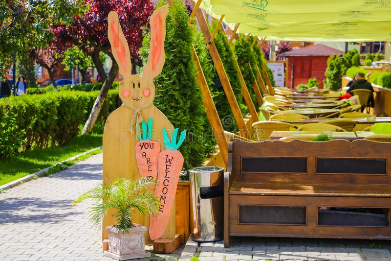 Sighisoara, Romania, May 13, 2019: Funny sign in a cafe on the terrace in the form of hares. Out of focus cafe visitors.  stock image