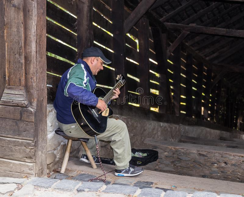 The street guitar player plays the guitar near the entrance to the tunnel, leading to the old town of Sighisoara in Romania stock photo