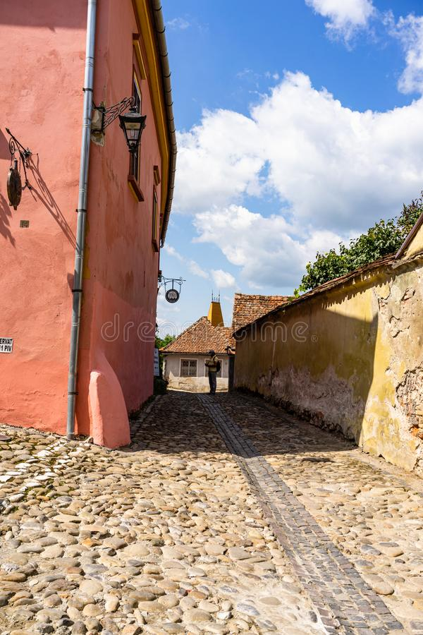 Sighisoara, Romania - 2019. Old street with cobblestone pavement and colorful houses in Sighisoara citadel. Lost man on the street royalty free stock photography