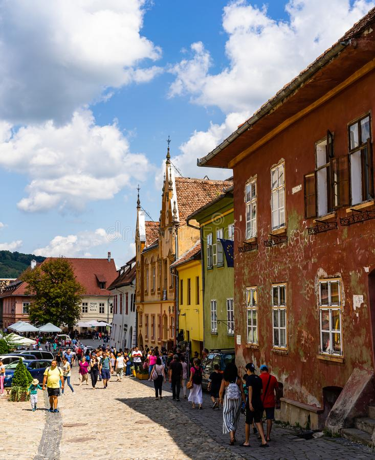 Sighisoara, Romania - 2019. People wandering on the streets of Sighisoara citadel old town. Streets with colorful houses royalty free stock photo