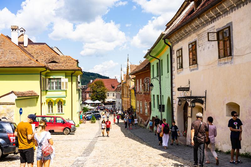 Sighisoara, Romania - 2019. People wandering on the streets of Sighisoara citadel old town. Streets with colorful houses royalty free stock image