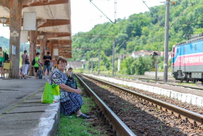 SIGHISOARA, RUMÄNIEN - 1. JULI 2016: Ältere Frau, die auf den Zug in Sighisoara, Rumänien wartet stockfoto