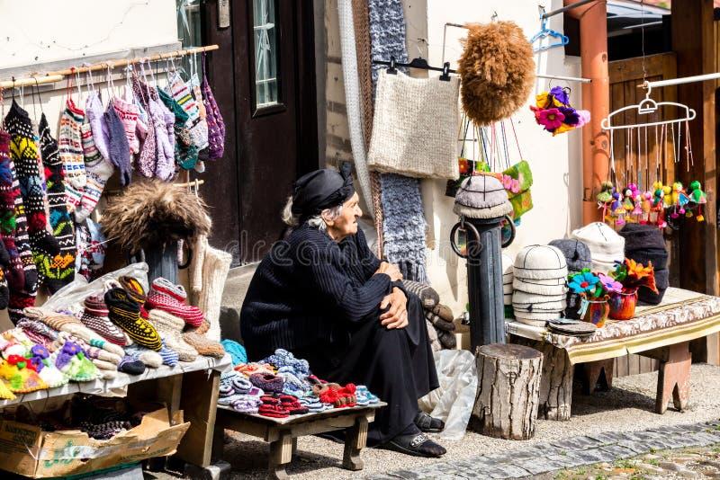 Sighnaghi, Georgia - 10 de junio de 2016: Vendedor mayor de la mujer que vende calcetines, los deslizadores de lana y los recuerd foto de archivo libre de regalías