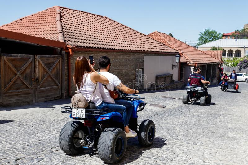 Happy tourists riding all terrain vehicle on street of the medieval town Sighnaghi. Sighnaghi, Kakheti, Georgia - May 2, 2018: Happy tourists riding all terrain royalty free stock images