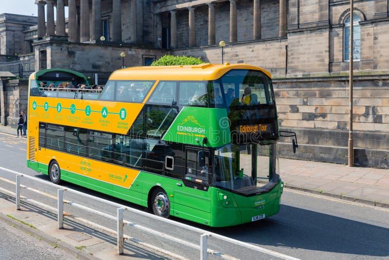 Sightbuss nära kunglig mil med historiska byggnader i Edinburg royaltyfri fotografi