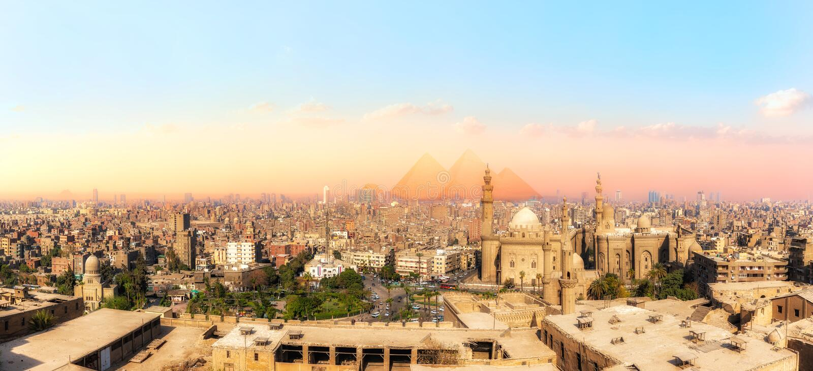 Sights of Cairo panorama: the Mosque-Madrassa of Sultan Hassan, the city view and the Pyramids royalty free stock image