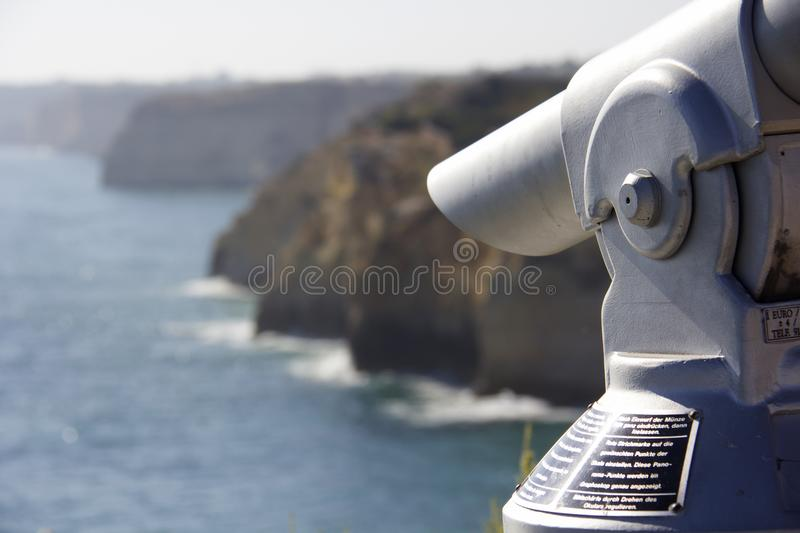 Sightseeing coin operated telescope. On the cliffs used for looking out into the sea in Carvoeiro, Algarve, Portugal. Wording on the telescope is instructions stock images