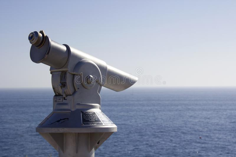 Sightseeing coin operated telescope. On the cliffs used for looking out into the sea in Carvoeiro, Algarve, Portugal. Wording on the telescope is instructions royalty free stock images