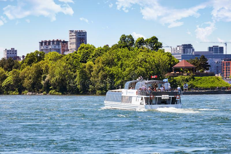 Sightseeing tour boat sailing on st. Lawrence river and montreal cirtyscape background in Quebec, Canada. Montreal, Canada - June, 2018: Sightseeing tour boat stock image
