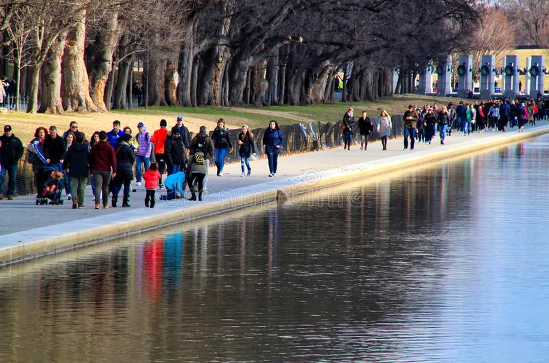 Sightseers in Washington, D.C. are reflected in the reflecting pool in the DC mall during winter morning in February. stock images