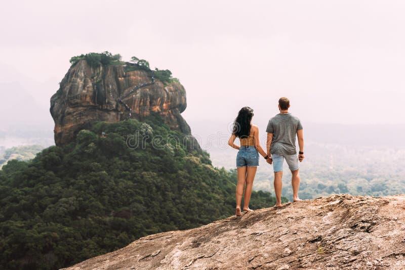 Ένα ζεύγος ερωτευμένο σε έναν βράχο θαυμάζει τις όμορφες απόψεις Αγόρι και κορίτσι στο βράχο Ερωτευμένα ταξίδια ζευγών Ζεύγος στη στοκ φωτογραφία
