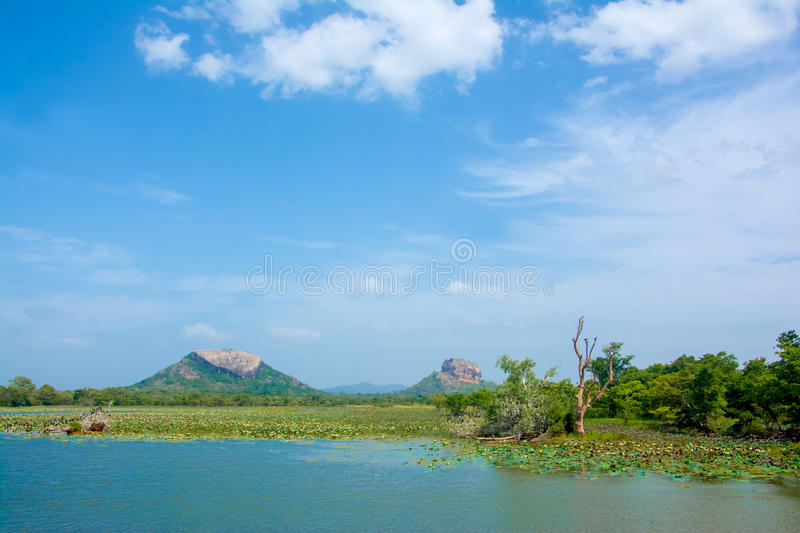 Sigiriya Rock Fortress View From Thalkote Lake. Spending the evening time around Thalkote lake is a popular way among the tourists stock photography
