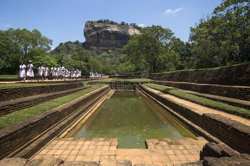 Sigiriya, Sri Lanka - March 23 2017: Students of a school class in white uniforms on a pathway at Lions Rock royalty free stock image