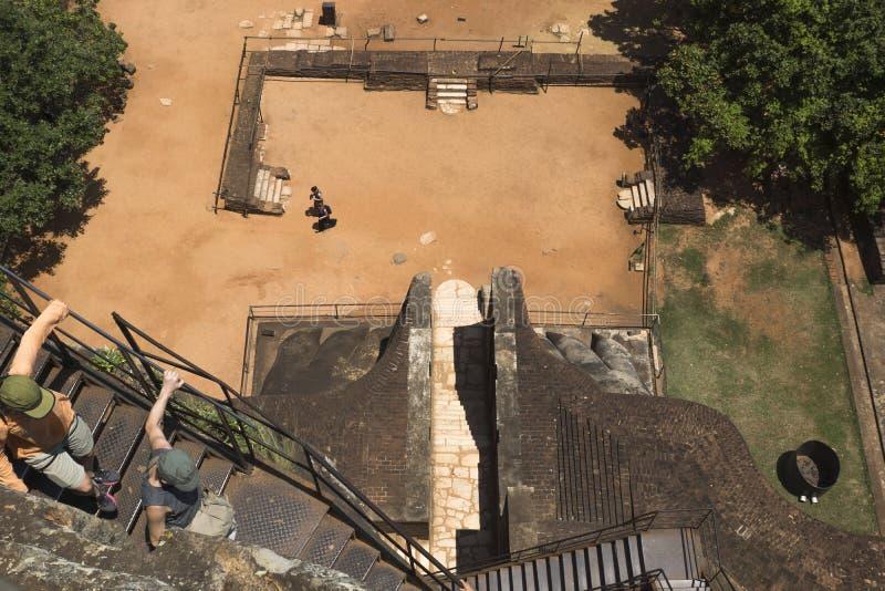 Sigiriya, Sri Lanka - March 23 2017: Tourist climbing down the stairs from Lions Rock royalty free stock photo