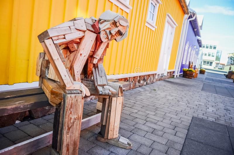 SIGLUFJORDUR, ISLAND - 15. August 2012: Sitzende hölzerne Statue mit buntem Hintergrund, Siglufjordur, Island stockfotos