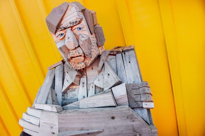 SIGLUFJORDUR, ISLAND - 15. August 2012: Sitzende hölzerne Statue mit buntem Hintergrund, Siglufjordur, Island lizenzfreie stockbilder