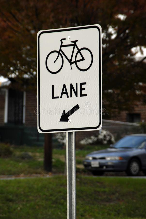 Sign on well traveled road changing one lane into bicycle lane stock images
