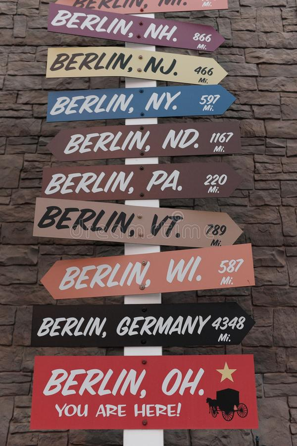 A sign in Berlin, Ohio points to other cities with the name `Berlin` around the world royalty free stock image