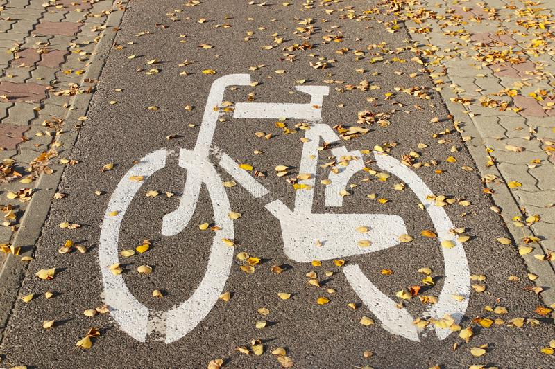 The sign is a bicycle path sprinkled with autumn fallen leaves. Road markings on the pavement of the sidewalk to separate the move stock photos