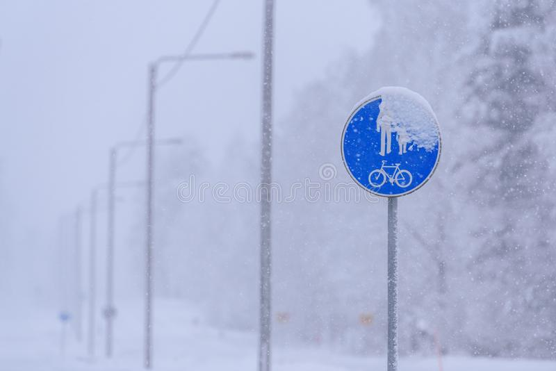 The sign of a bike path and a pedestrian on the road in winter at Tuupovaara, Finland. Background bad bicycle big biking blue board car child cold concept royalty free stock images