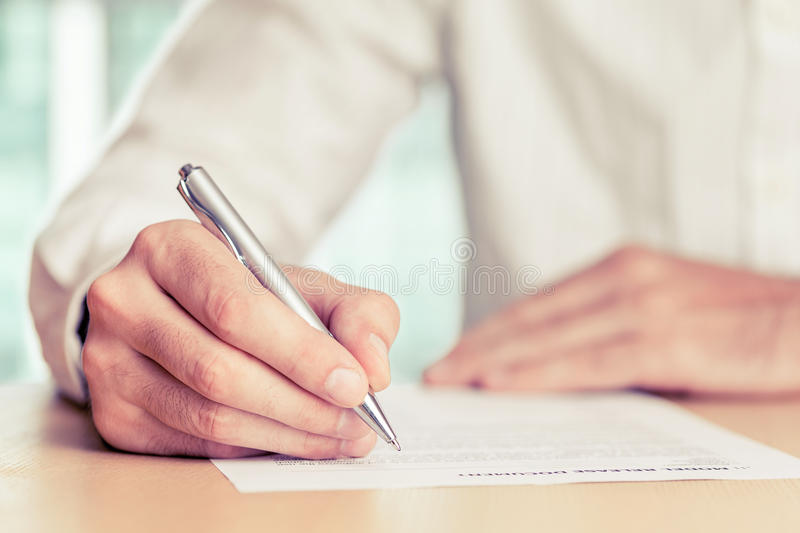 Sign. Businessman signing a document. Tinted photo, shallow depth of field royalty free stock photography