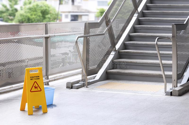 Sign caution warning floor wet and cleaner equipment on the stair in skytrain station. Safety sign with text caution stock photography