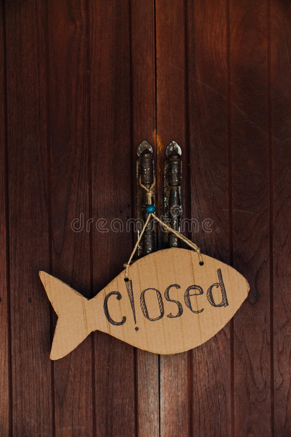 Sign is closed in the form of fish from cardboard. Hanging on the door on the rope.  royalty free stock photography