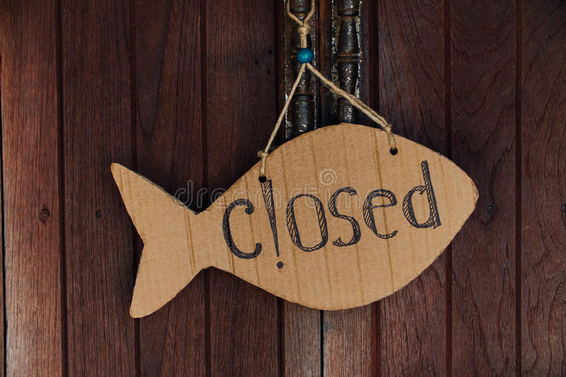 Sign is closed in the form of fish from cardboard. Hanging on the door on the rope.  stock image