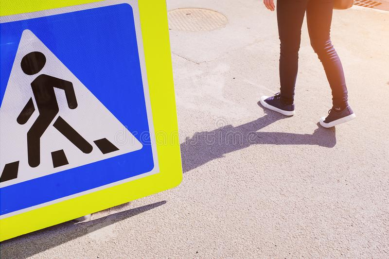 The sign of the crosswalk lies on the asphalt, is not installed. Next is a girl stock photos