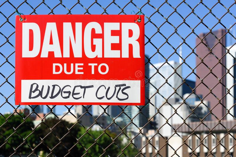 Sign danger due to budget cuts hanging on the fence royalty free stock photography