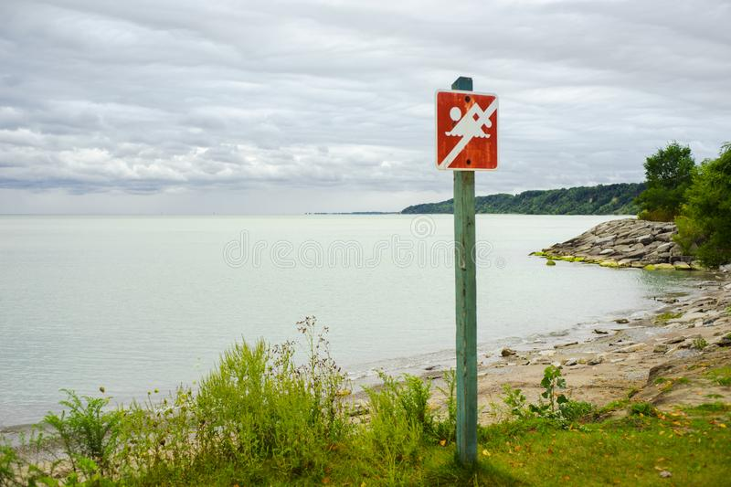 A sign declaring beach closed to swimming. A sign declaring the beach is closed to swimming at Scarborough Bluffs near Toronto stock images