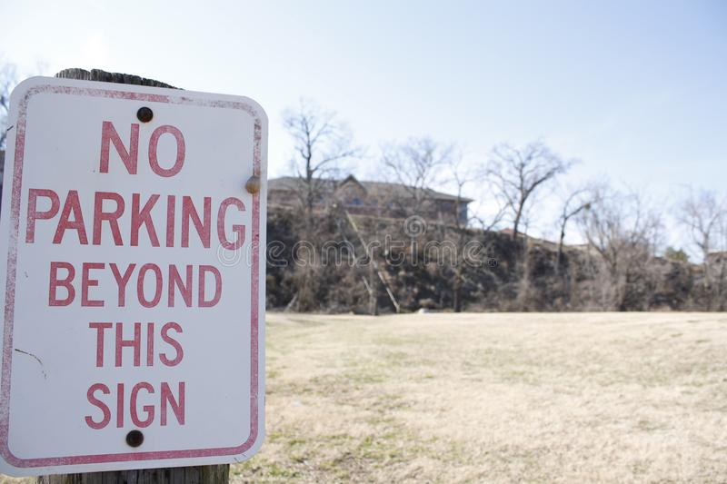 No Parking Beyond This Sign. A sign dictating that no one should park here in this empty field stock photo