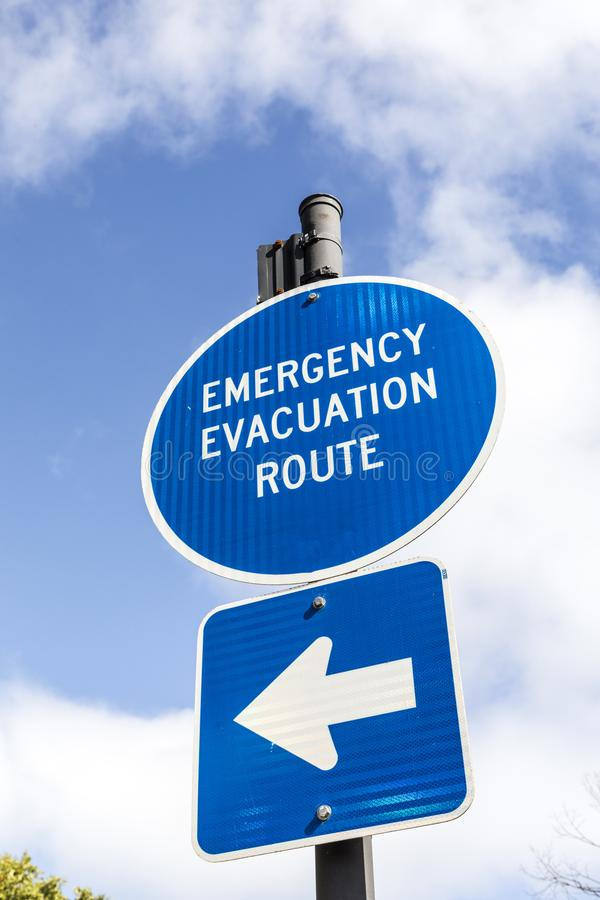 Sign emergency evacuation route. In blue under blue sky stock images