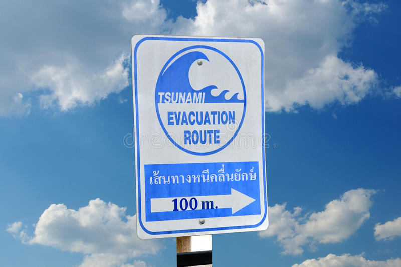 Sign an evacuation route at danger of a tsunami. Sign an evacuation route at danger of a tsunami on a blue sky background stock photos