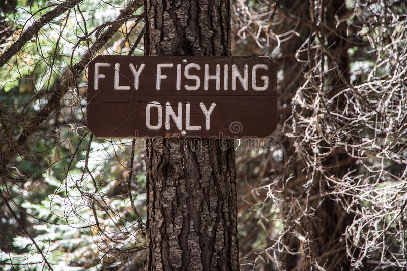 Sign for Fly Fishing Only. A wood sign indicating FLY FISHING ONLY along the Metolius River in the central Oregon Cascade Mountains royalty free stock photos