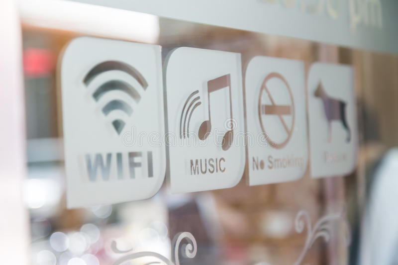 Sign (Free Wifi,Music,No smoke,Pet in). Sign on glass door (Free Wifi,Music,No smoke,Pet in stock photography