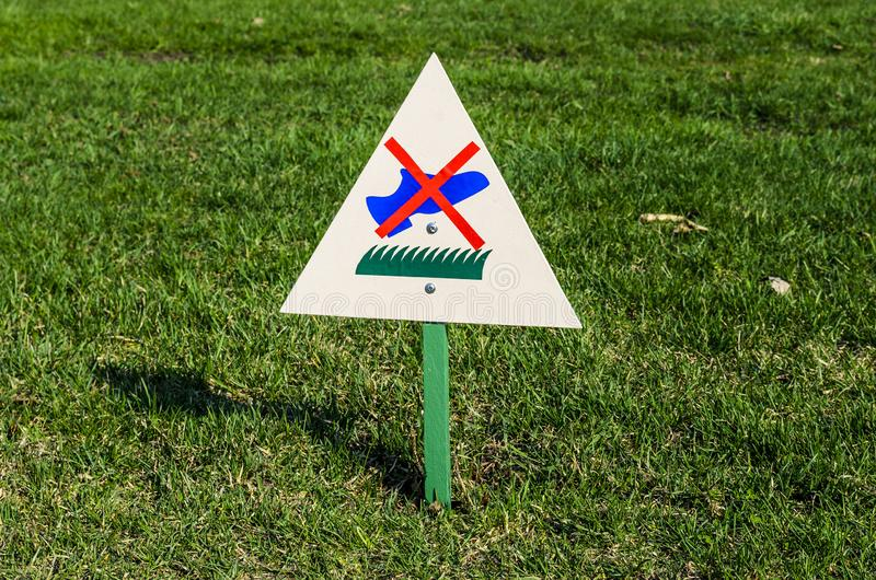 The sign on the grass prohibiting to walk on the grass. a Billboard. Forbidding stock photos