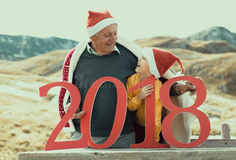 2018 sign in the hands of a senior caucasian man and little boy royalty free stock photography
