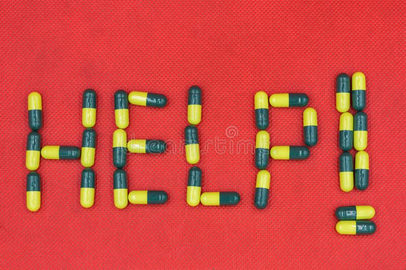 Sign Help made from medicine capsules closeup stock photography