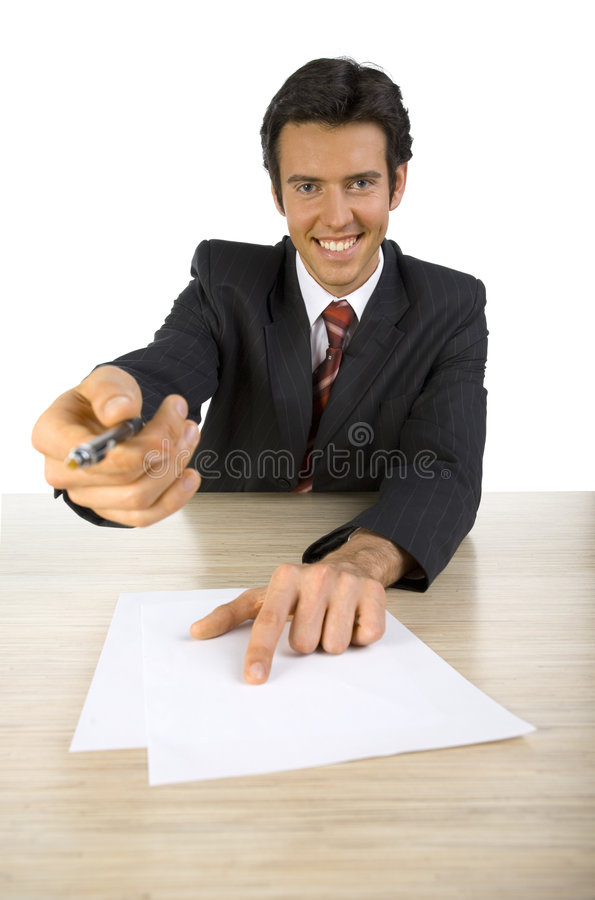 Sign here. Smiling, handsome businessman. Seating behind desk, giving a pen. Looking at camera. White background, front stock photography