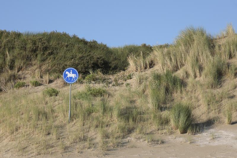 Sign indicating a horse riding trail in the dunes. A sign indicating there is a horse riding trail through the dunes. Must be a great feeling riding a horse royalty free stock image