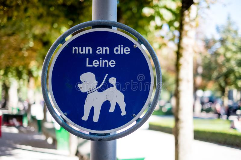 Sign indicating to keep the dogs connected to their leash stock photography