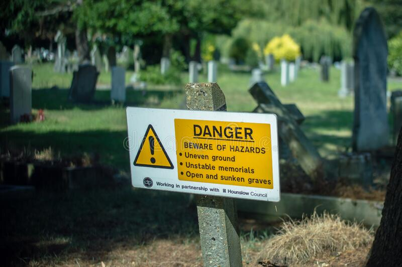 London. United Kingdom. 2017. London Cemetary. Hounslow. Sign informing visitors of dangers resulting from uneven ground and unstable memorials royalty free stock photo