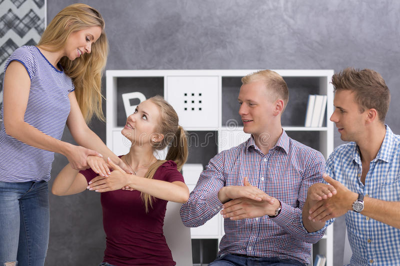 Sign language teacher correcting her students royalty free stock photography