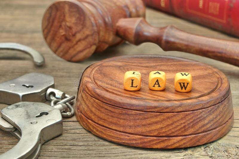 Sign LAW on the Soundboard, Judges Gavel, handcuffs and book in stock image