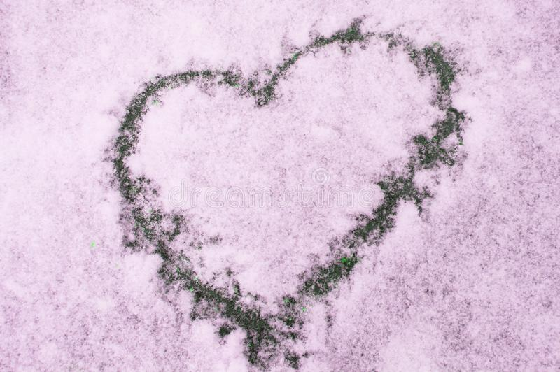 Sign of love-heart painted on snow, pastel pink background, Valentine's day stock image