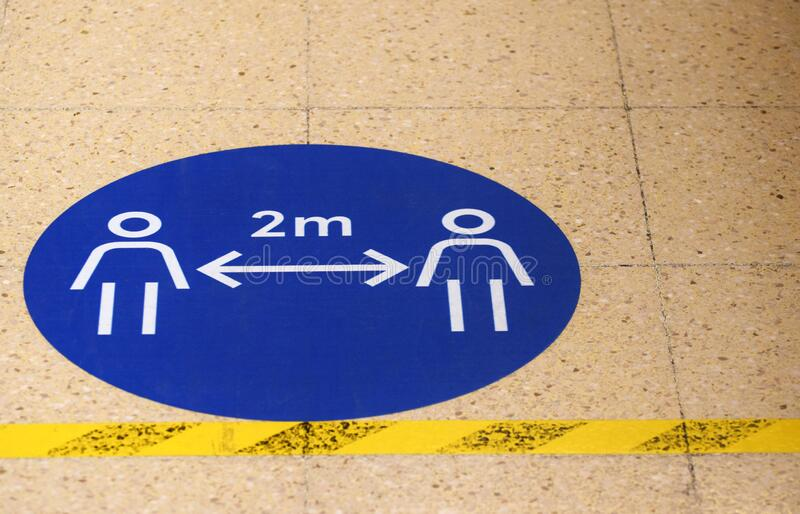 A sign / marker on a grocery supermarket shop floor showing the social distancing spacing of 2 metres royalty free stock photography