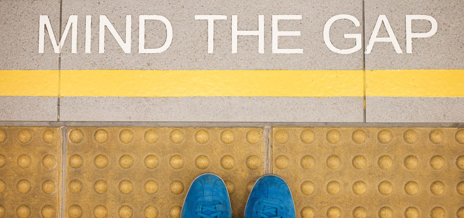 The sign Mind the gap painted on train station's platform edge royalty free stock photos