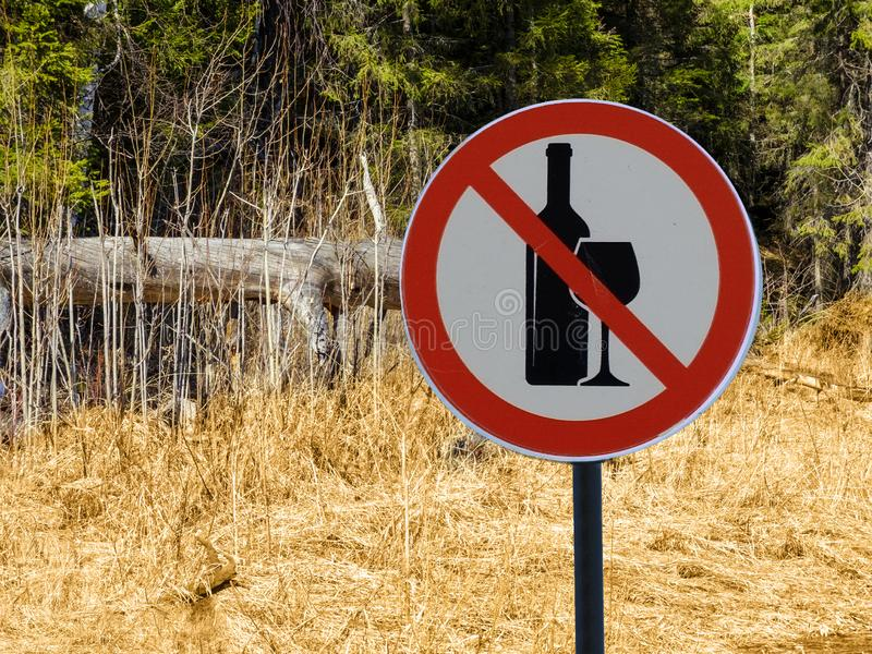 Sign no alcohol on the background of forest and dry grass and trees. royalty free stock photos